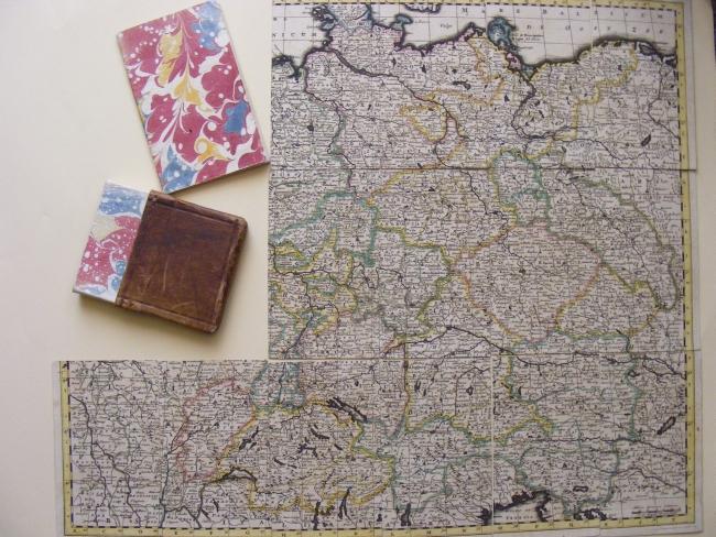 Oben das ausgelegte Landkarten-Puzzle sowie das Schachtelunterteil und das Beiheft